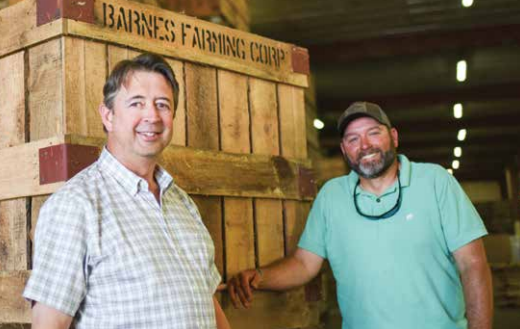 Two men posing in front of crate labeled Barnes Farming Corp